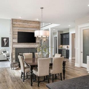 シカゴの中サイズのビーチスタイルのおしゃれなダイニングキッチン (ベージュの壁、無垢フローリング、タイルの暖炉まわり、茶色い床、両方向型暖炉) の写真