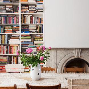 Geräumige Shabby-Chic-Style Wohnküche mit weißer Wandfarbe, braunem Holzboden, Kamin und Kaminsims aus Stein in New York