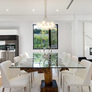 Ejemplo de comedor contemporáneo, abierto, con paredes blancas, suelo de madera clara, chimenea lineal y suelo beige
