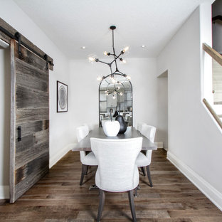 Example of a farmhouse medium tone wood floor and brown floor dining room design in Toronto with white walls