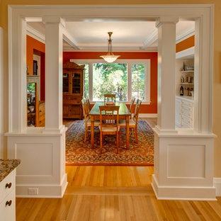 Imagen de comedor de estilo americano, cerrado, con paredes rojas y suelo de madera en tonos medios