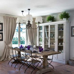 Diseño de comedor romántico con paredes blancas y suelo de ladrillo