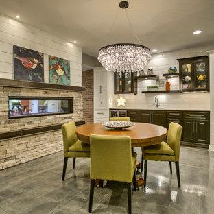 Foto di una grande sala da pranzo aperta verso il soggiorno classica con pareti grigie, camino bifacciale, pavimento in cemento, cornice del camino in pietra e pavimento grigio