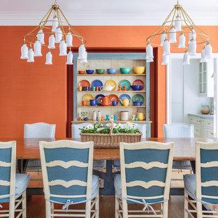 Immagine di una grande sala da pranzo aperta verso il soggiorno country con pareti arancioni, parquet chiaro e pavimento marrone
