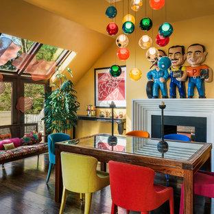 Aménagement d'une salle à manger éclectique avec un sol en bois foncé, une cheminée double-face, un manteau de cheminée en pierre et un mur orange.