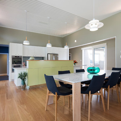 Inspiration for a mid-sized contemporary medium tone wood floor kitchen/dining room combo remodel in Brisbane with green walls