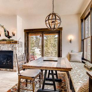 Immagine di una piccola sala da pranzo aperta verso il soggiorno stile rurale con pavimento in gres porcellanato, camino classico, cornice del camino in pietra e pavimento bianco