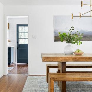 Imagen de comedor costero, pequeño, abierto, con paredes blancas, suelo de madera oscura, chimenea tradicional, marco de chimenea de ladrillo y suelo marrón