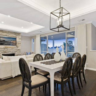 Design ideas for a transitional dining room in Perth with beige walls, dark hardwood floors, a ribbon fireplace, a stone fireplace surround and brown floor.