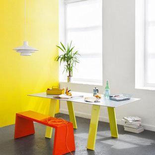 Immagine di una sala da pranzo minimal con pareti gialle e pavimento in cemento