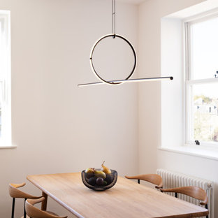 This is an example of a contemporary dining room in London with white walls, medium hardwood flooring and beige floors.