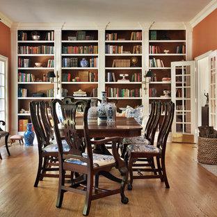 Idee per una grande sala da pranzo chic chiusa con pareti arancioni, pavimento in legno massello medio, camino classico, cornice del camino piastrellata e pavimento marrone