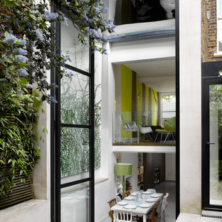 This is an example of a contemporary kitchen/dining room in London with white walls.