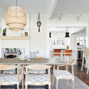 Dining room - beach style dark wood floor and brown floor dining room idea in San Francisco with beige walls and a wood stove