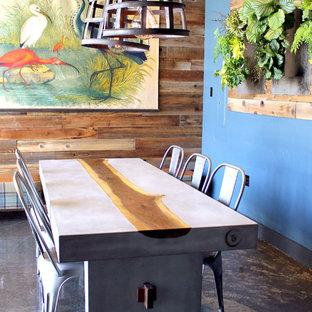 Idee per una sala da pranzo industriale chiusa e di medie dimensioni con pareti blu, pavimento in cemento, nessun camino e pavimento marrone