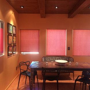 Esempio di una sala da pranzo aperta verso la cucina minimal di medie dimensioni con pareti arancioni, pavimento in terracotta e pavimento rosso