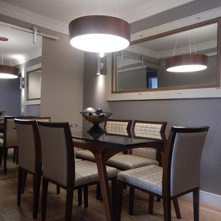 Immagine di una piccola sala da pranzo design chiusa con pareti grigie, pavimento in compensato e nessun camino