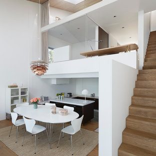 Example of a large danish medium tone wood floor kitchen/dining room combo design in Stockholm with white walls and no fireplace