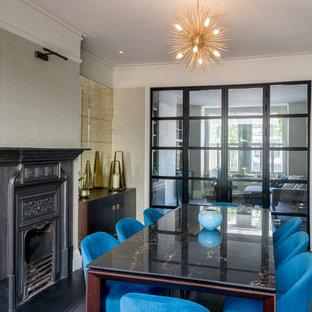 ロンドンの中くらいのエクレクティックスタイルのおしゃれなダイニング (白い壁、濃色無垢フローリング、標準型暖炉、金属の暖炉まわり、黒い床) の写真