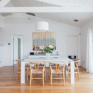 Example of a mid-sized trendy beige floor and light wood floor great room design in Tampa with white walls and no fireplace