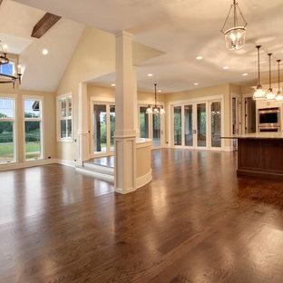 Foto di un'ampia sala da pranzo aperta verso il soggiorno country con pareti beige, pavimento in legno massello medio, camino classico e cornice del camino in pietra
