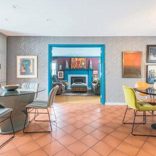 Foto di una grande sala da pranzo aperta verso la cucina minimal con pareti grigie, pavimento in terracotta, camino classico, cornice del camino piastrellata e pavimento rosso