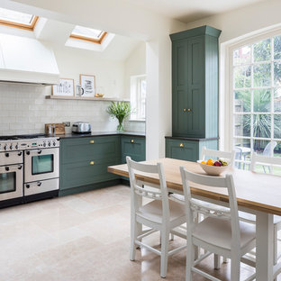 Classic kitchen/dining room in London with white walls and beige floors.