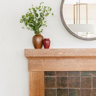 Imagen de comedor de estilo americano, de tamaño medio, cerrado, con paredes blancas, suelo de madera clara, chimenea tradicional y marco de chimenea de baldosas y/o azulejos
