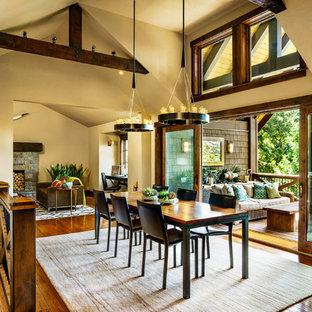 Imagen de comedor de cocina actual, grande, con paredes beige, suelo de madera en tonos medios, chimenea tradicional y marco de chimenea de piedra