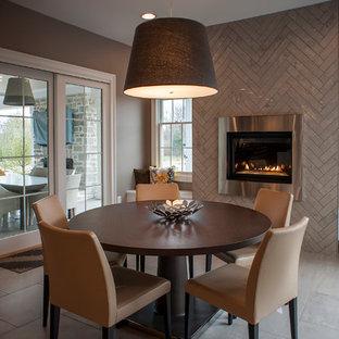 Immagine di una sala da pranzo contemporanea con pareti grigie, cornice del camino piastrellata e pavimento con piastrelle in ceramica