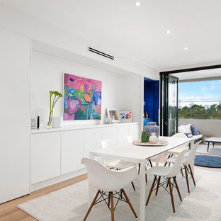Contemporary dining room in Sydney with white walls, medium hardwood floors, no fireplace and brown floor.