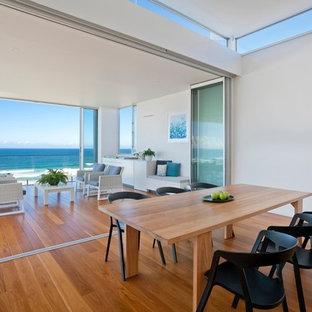 Idée de décoration pour une salle à manger design avec un mur blanc, un sol en bois brun et un sol orange.
