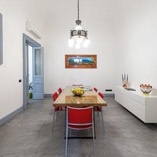Idee per una sala da pranzo design chiusa e di medie dimensioni con pareti bianche, pavimento in cemento, nessun camino e pavimento grigio