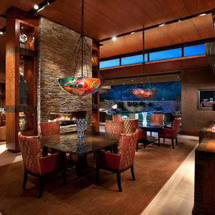 Ispirazione per una grande sala da pranzo aperta verso il soggiorno contemporanea con pareti marroni, camino bifacciale, pavimento con piastrelle in ceramica e cornice del camino in pietra