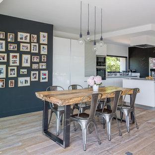 Idées déco pour une grande salle à manger ouverte sur la cuisine contemporaine avec un sol en bois clair, un mur noir et aucune cheminée.
