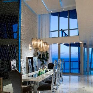 Imagen de comedor contemporáneo con paredes blancas y suelo de mármol