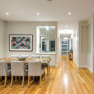 This is an example of a contemporary dining room in Adelaide with beige walls, medium hardwood floors and beige floor.