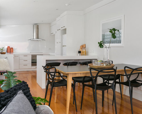 Photo Of A Contemporary Open Plan Dining In Hobart With White Walls And  Medium Hardwood Floors