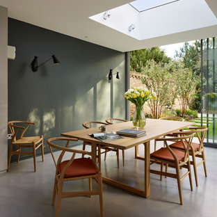 Inspiration for a contemporary dining room in London with concrete flooring and grey walls.