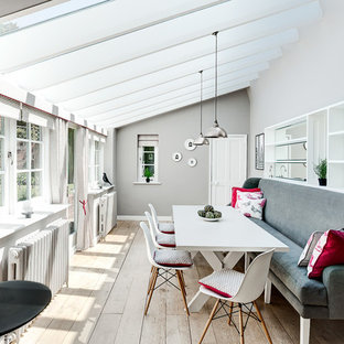 Photo of a contemporary dining room in London with grey walls and medium hardwood flooring.