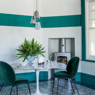 Стильный дизайн: отдельная столовая среднего размера в современном стиле с разноцветными стенами, полом из керамической плитки, печью-буржуйкой и разноцветным полом - последний тренд
