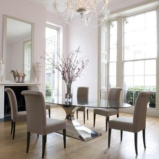 Réalisation d'une grande salle à manger design avec un mur rose, un sol en bois clair, une cheminée standard et un manteau de cheminée en plâtre.