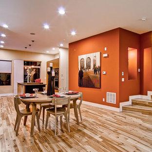 Cette photo montre une salle à manger ouverte sur la cuisine tendance avec un mur orange et un sol en bois brun.