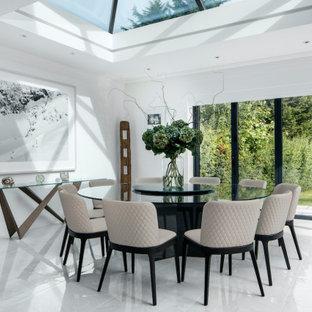 Immagine di una grande sala da pranzo aperta verso il soggiorno minimal con pareti bianche, pavimento bianco e pavimento in marmo