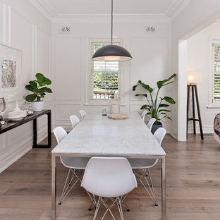 Inspiration for a mid-sized scandinavian laminate floor and gray floor great room remodel in Other with white walls