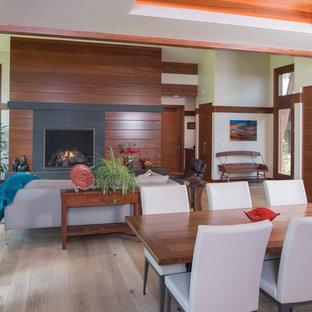 Ejemplo de comedor de cocina actual, de tamaño medio, con paredes blancas, suelo de madera clara, chimenea tradicional y marco de chimenea de madera