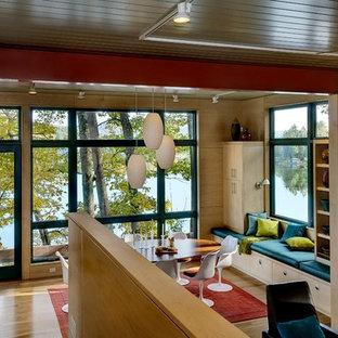 Immagine di una sala da pranzo minimal con pavimento in legno massello medio e stufa a legna
