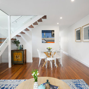 Photo of a mid-sized contemporary dining room in Sydney with white walls, no fireplace, brown floor and medium hardwood floors.