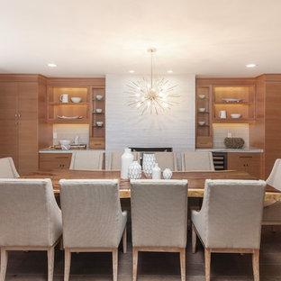 Ejemplo de comedor actual, de tamaño medio, cerrado, con paredes grises, suelo de madera clara, chimenea tradicional, marco de chimenea de hormigón y suelo marrón