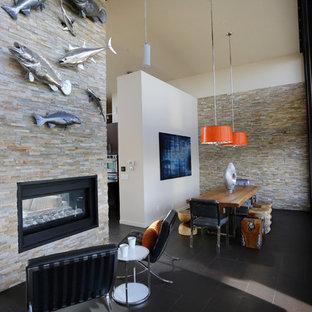 Esempio di una sala da pranzo aperta verso il soggiorno design di medie dimensioni con pareti bianche, pavimento in gres porcellanato, camino bifacciale, cornice del camino in pietra e pavimento nero